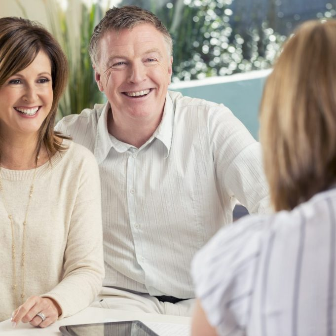 Happy mature couple meeting with advisor at home. Could be a lawyer or financial advisor.  There is a laptop and digital tablet on the table. Home interior can be seen. Couple are happy and smiling.